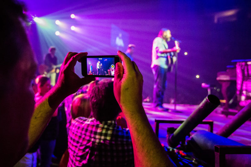 A fan takes a photo of Mac Powell during the Third Day and Friends concert at Infinite Energy Center in Atlanta, Georgia