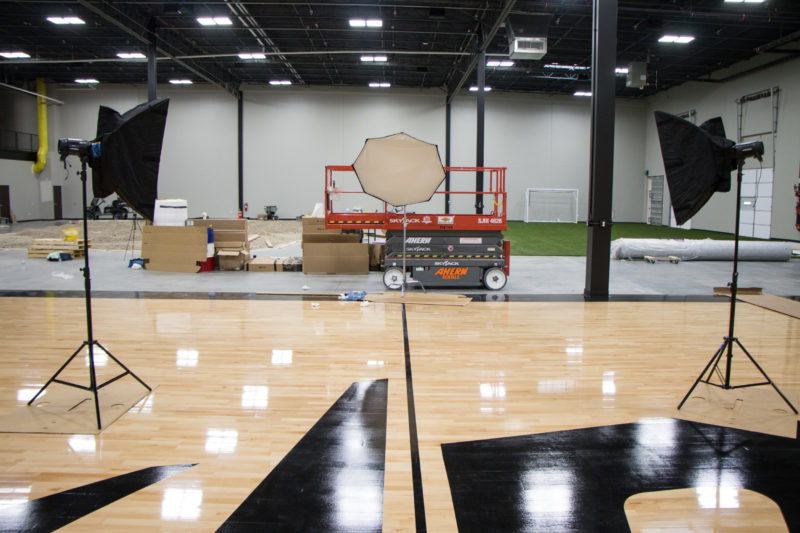 Studio lights set up on the Dude Perfect basketball court at their headquarters in Frisco, Texas